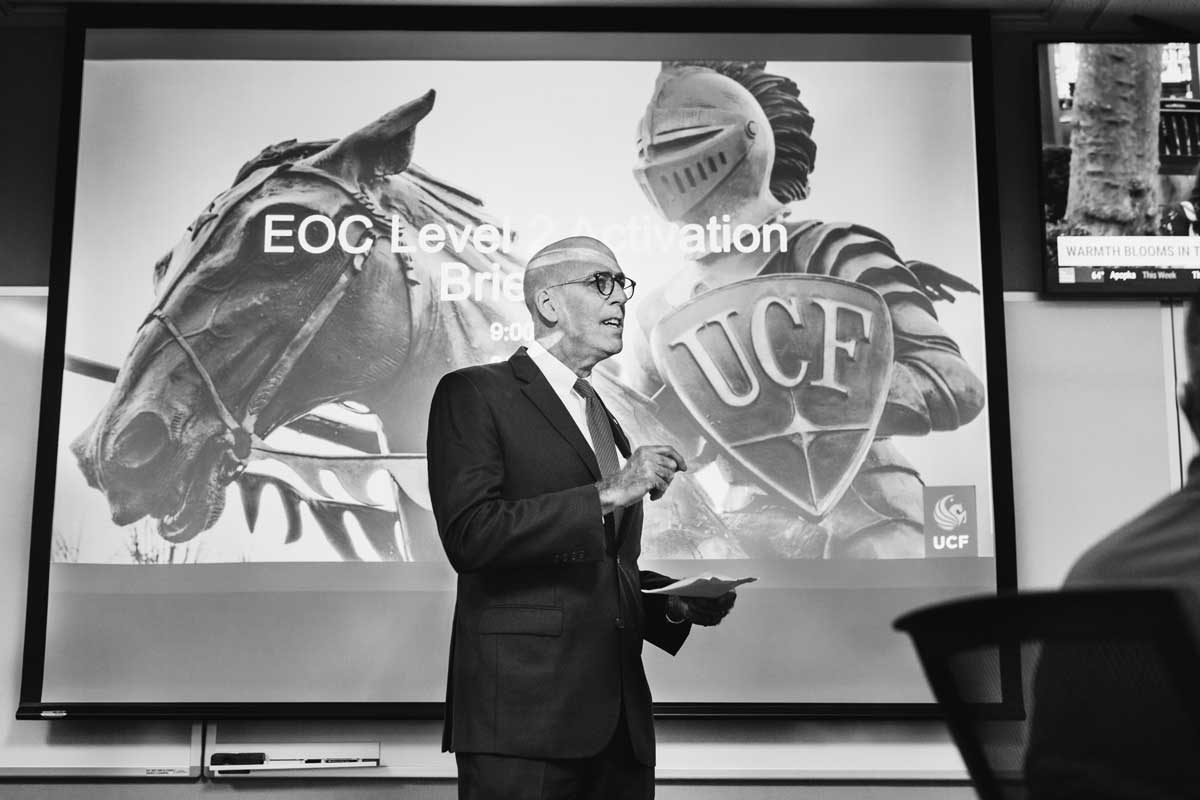 black and white photo of UCF Interim President Thad Seymour Jr. standing in front of a powerpoint screen