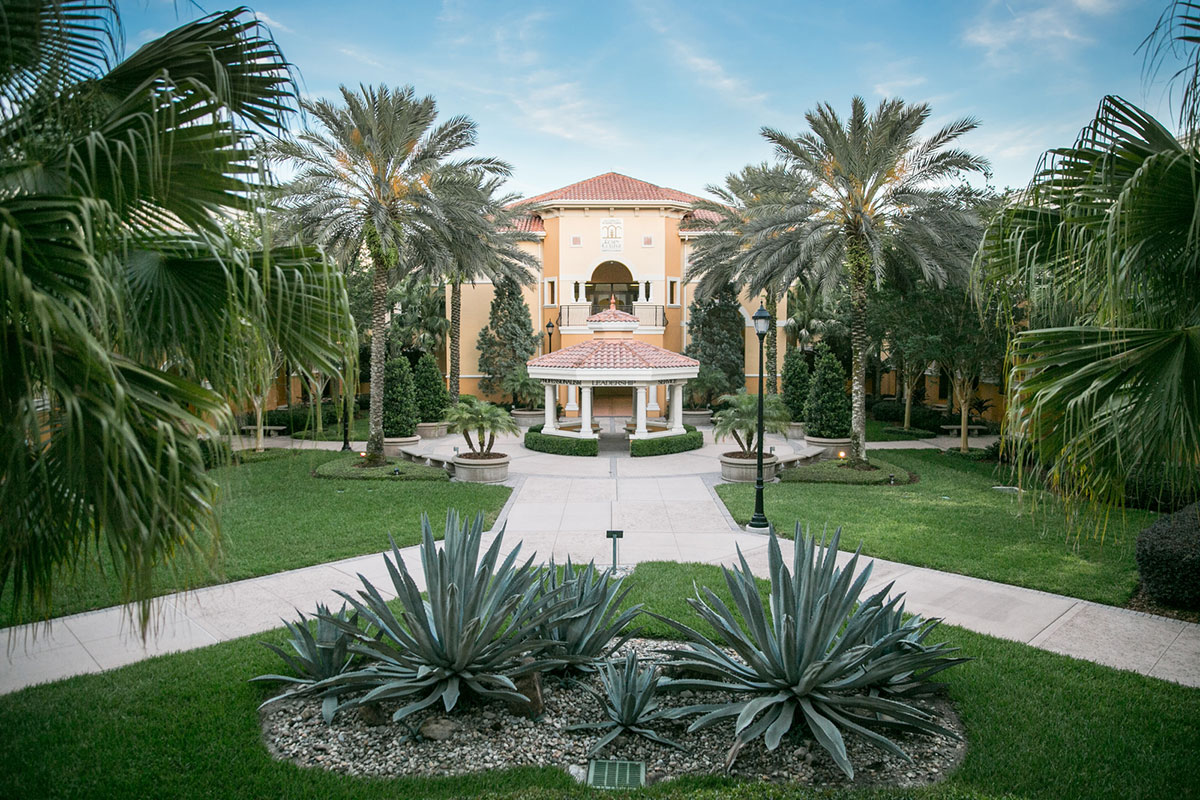 A Spanish-mediterranean-style building is surround by lush green grass and palm trees.