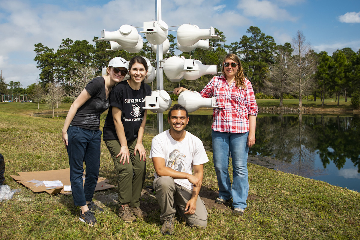 Four students stand in front of a pole with bird houses attached.