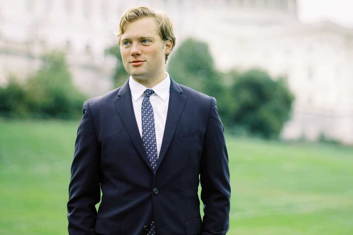 blonde man wearing business suit and tie stands in front of US Capitol Building