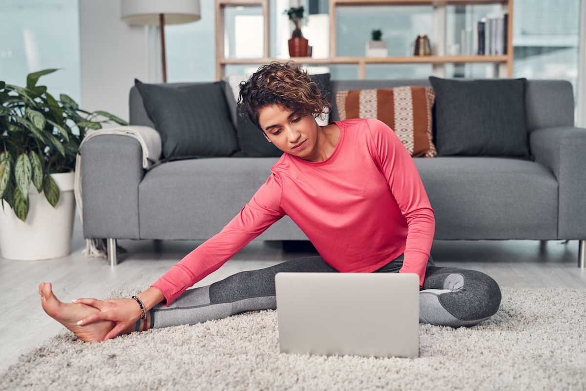Full length shot of an attractive young woman multitasking and using a laptop while stretching in her living room