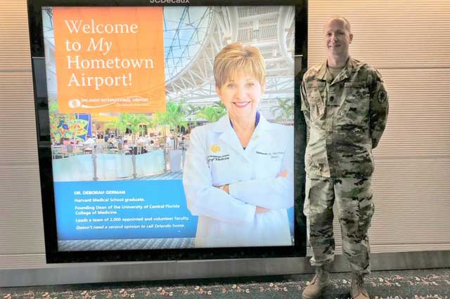 Man in military fatigues stands next to large advertisement in Orlando International Airport