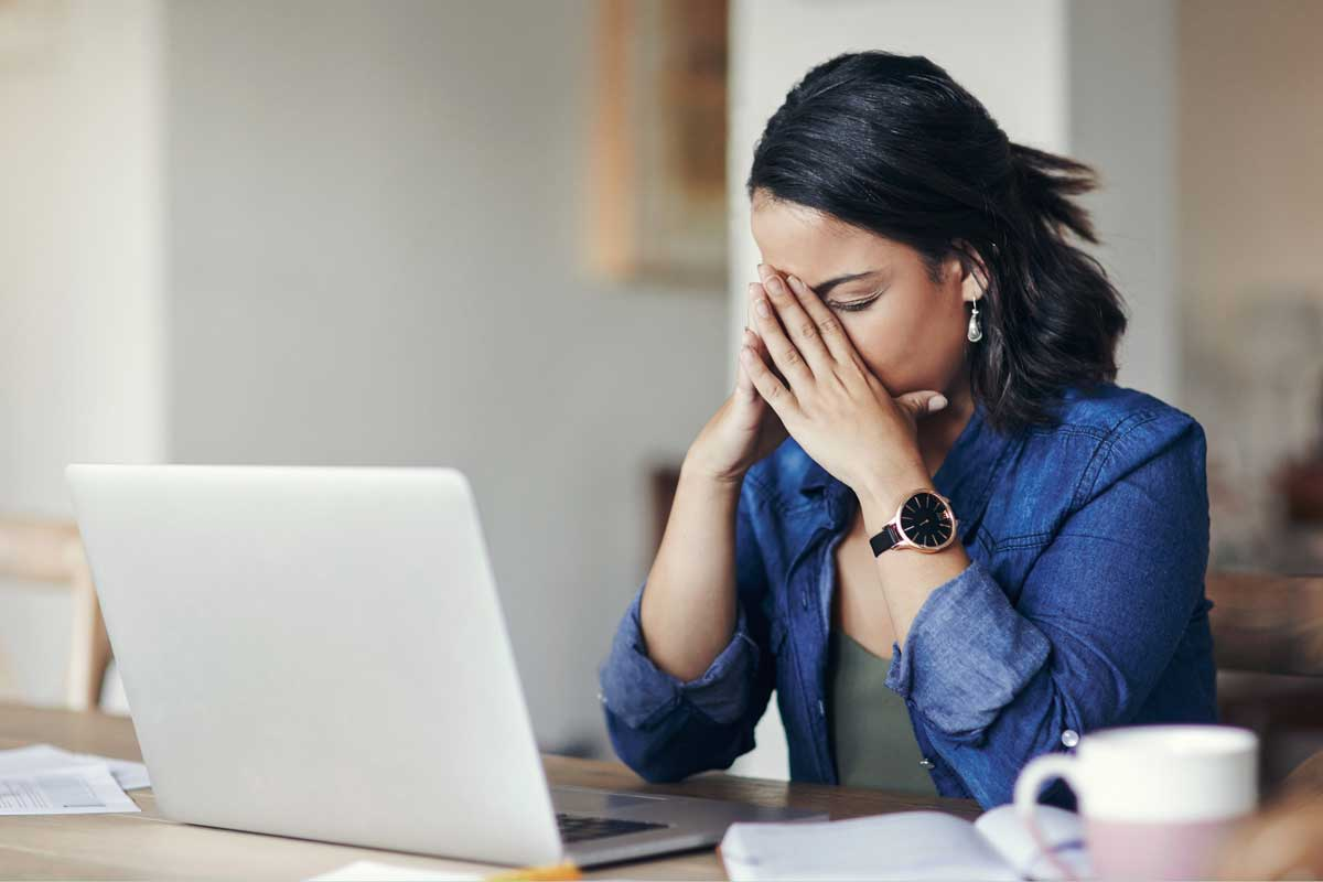 Woman buries face in her hands as she sits at a desk with laptop in front of her