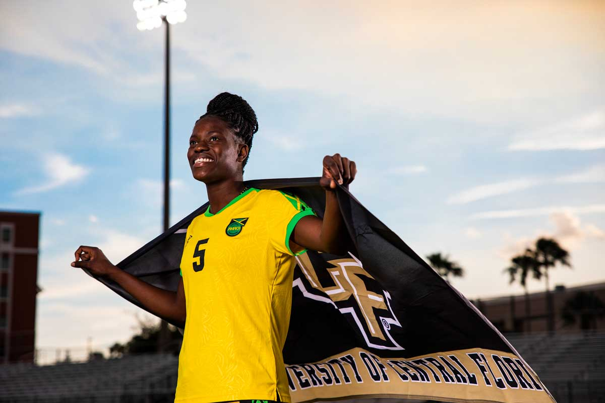 Konya Plummer, wearing yellow Jamaica uniform, drapes UCF flag around her shoulders and stands proudly
