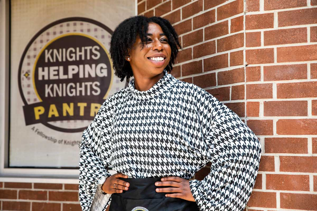Naseeka Dixon stands in front of Knights Pantry brick wall