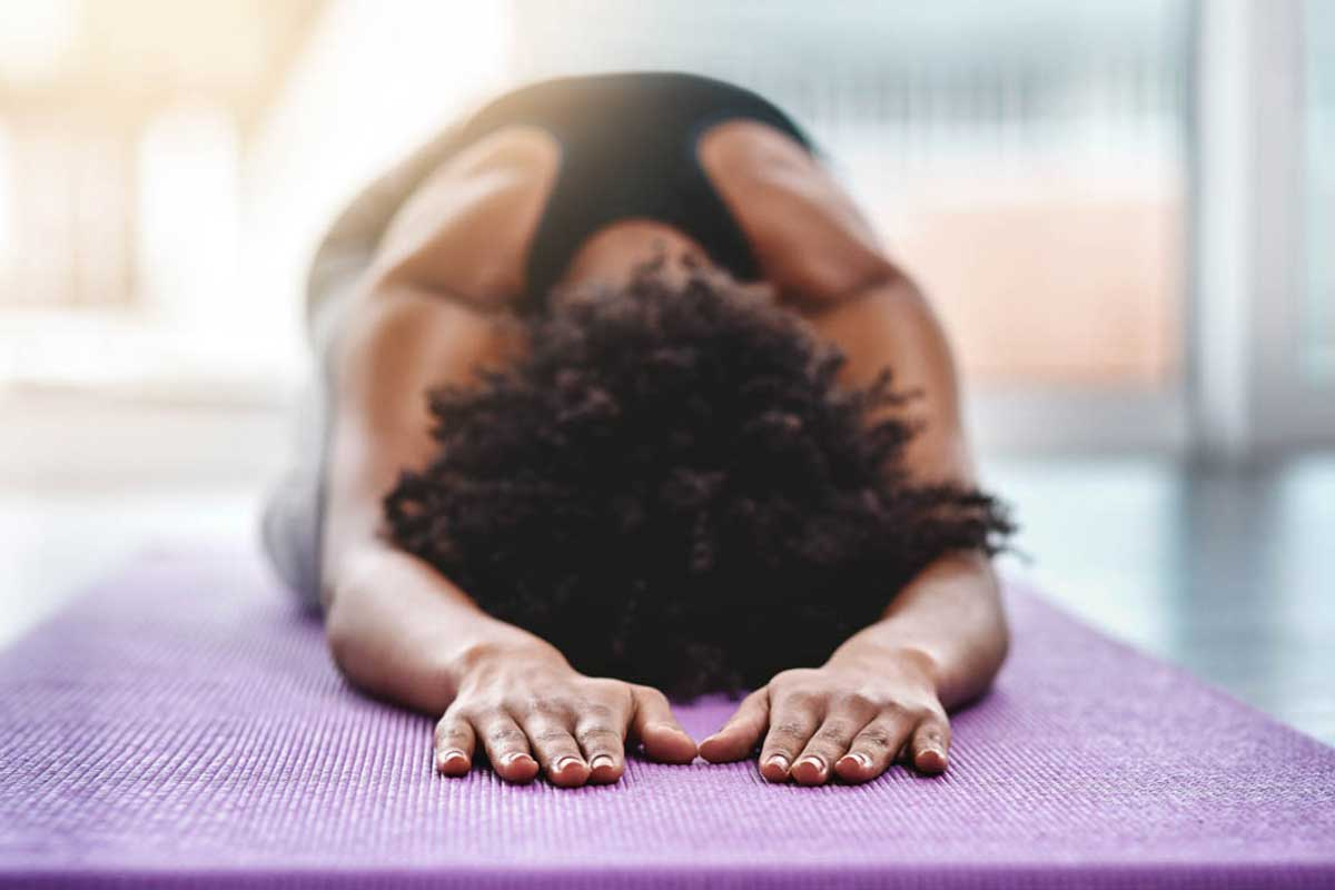 woman in child's pose on yoga mat