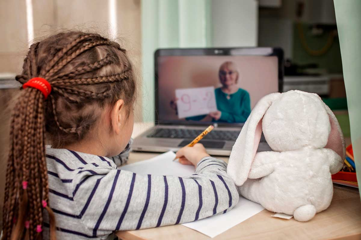 Young girl with braided hair sits at a table while holding a pencil in hand with a laptop in front of her
