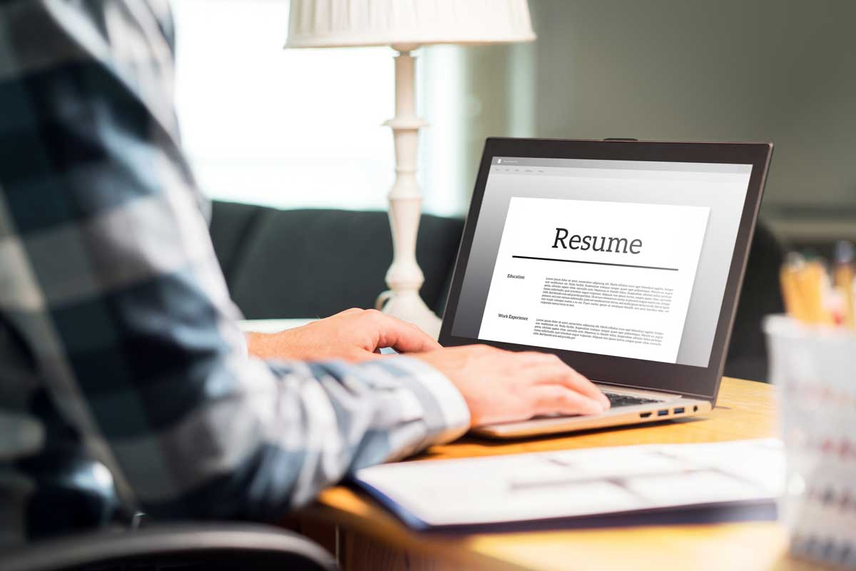 person sits at desk in front of laptop with resume