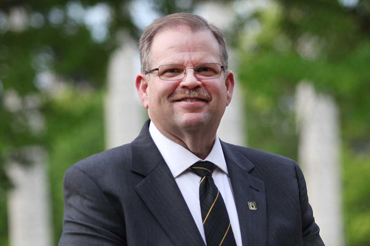 Man with glasses and wearing a suit and tie stands outside