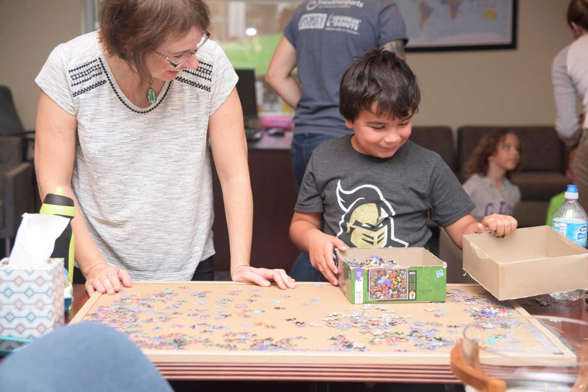 Young boy stands at table with unfinished puzzle
