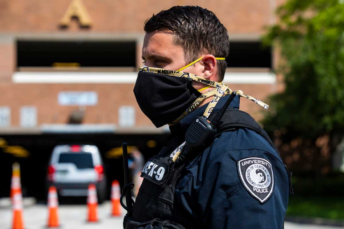 UCF Police officer wears black face mask with UCF theme tie strings, standing outside Garage A