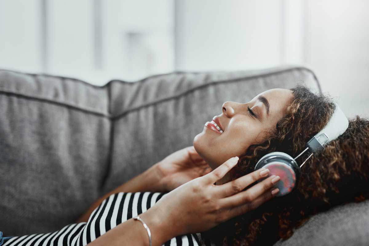 woman relaxes on couch with headphones