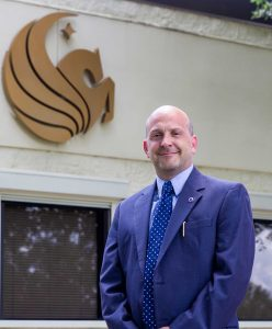 Portrait of Joe Thalheimer in front of Pegasus symbol on building