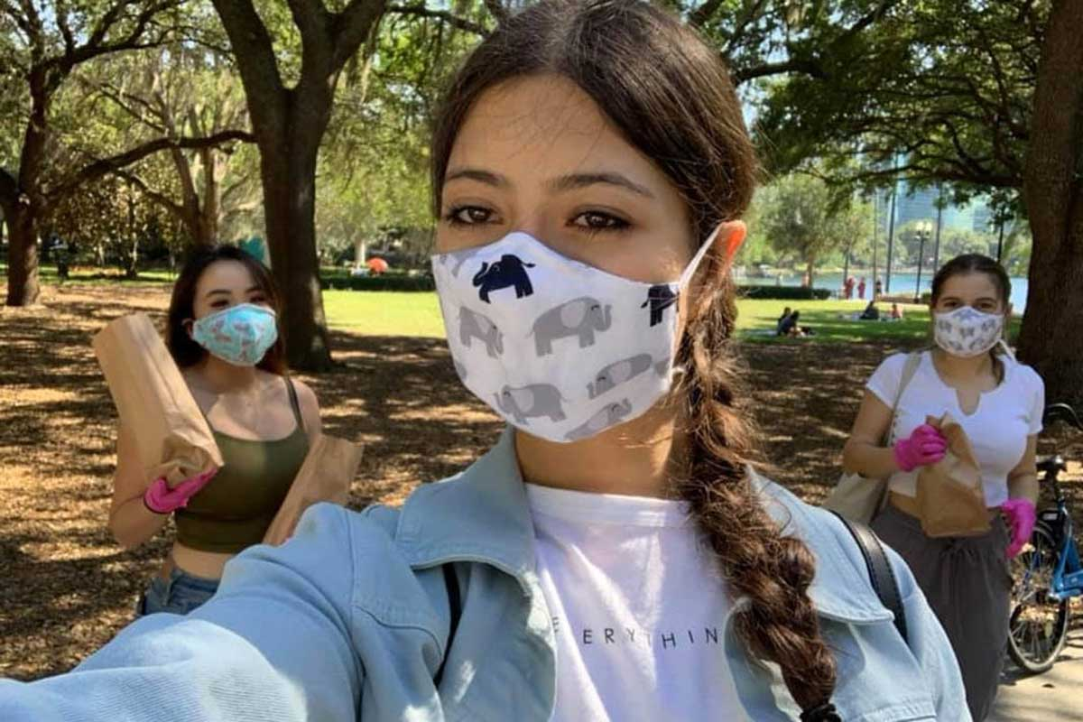Three women wearing face masks stand outside