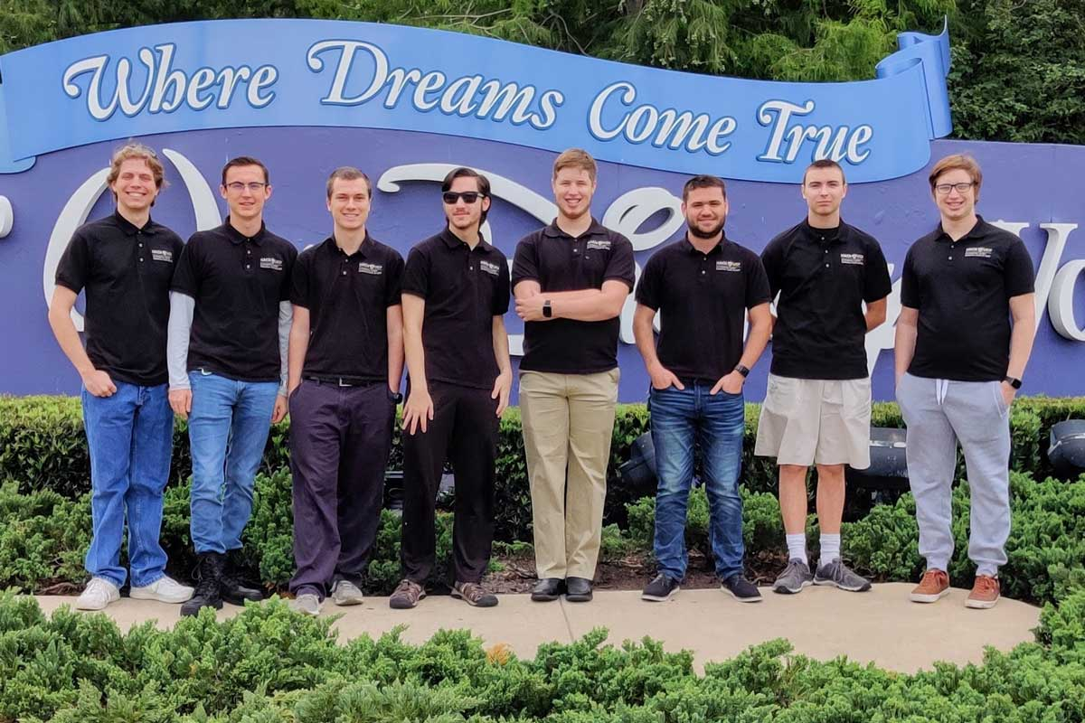 8 members of UCF cyber defense team stand shoulder to shoulder in front of Walt Disney World sign