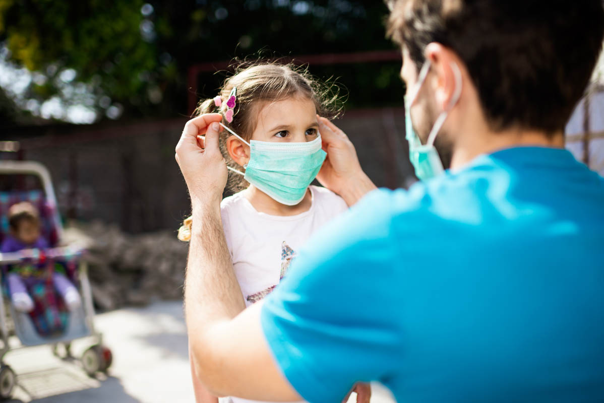 Father putting a mask on his daughter.