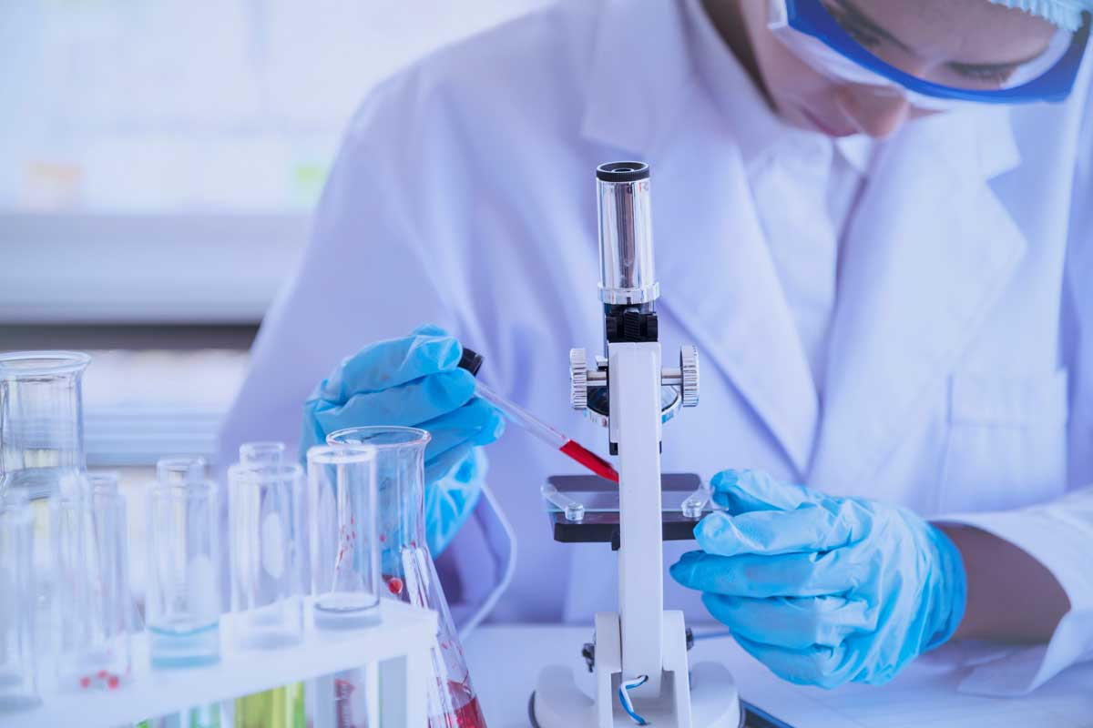 Researcher in lab wearing white coat stands next to microscope
