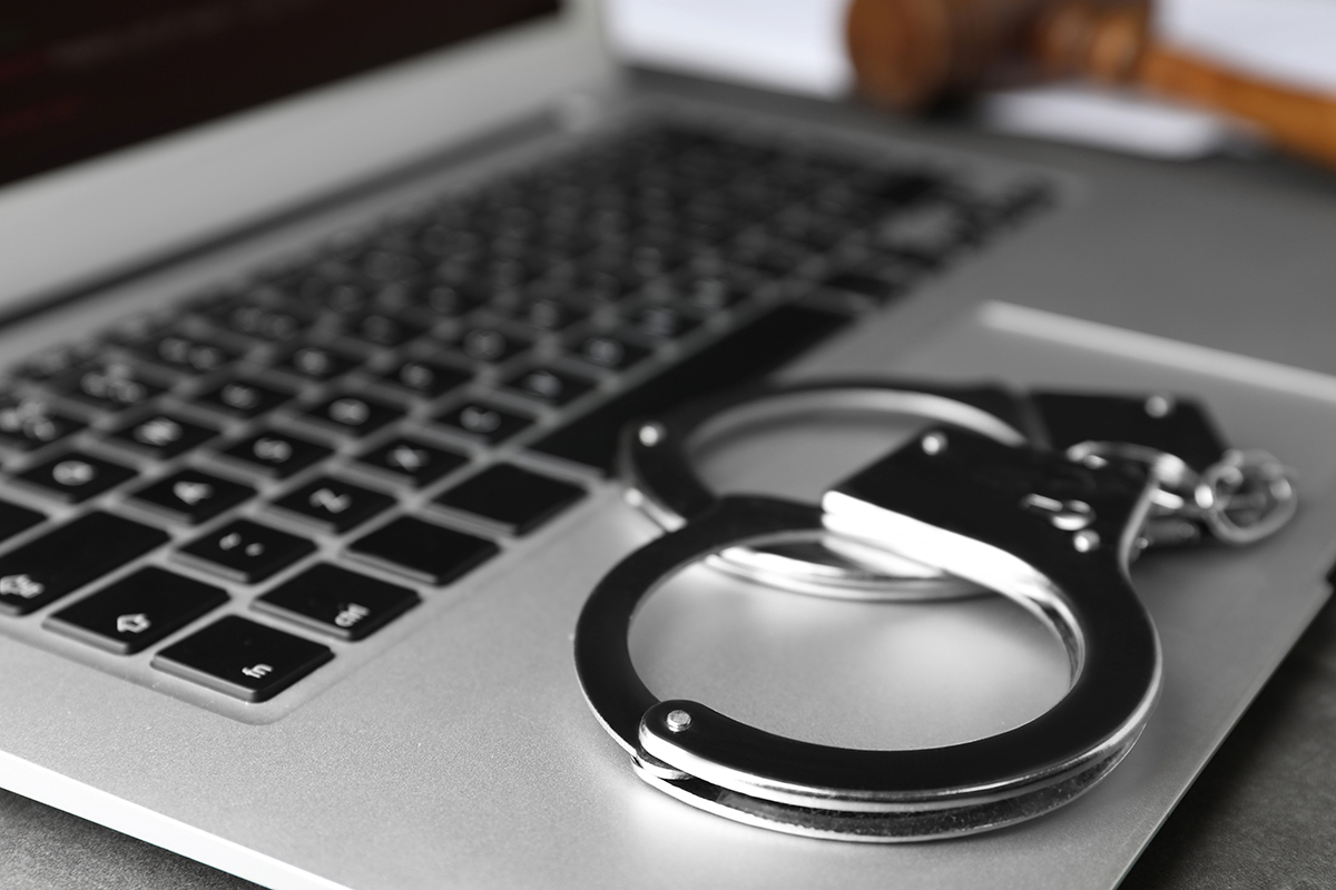 A picture of handcuffs on top of a laptop's keyboard