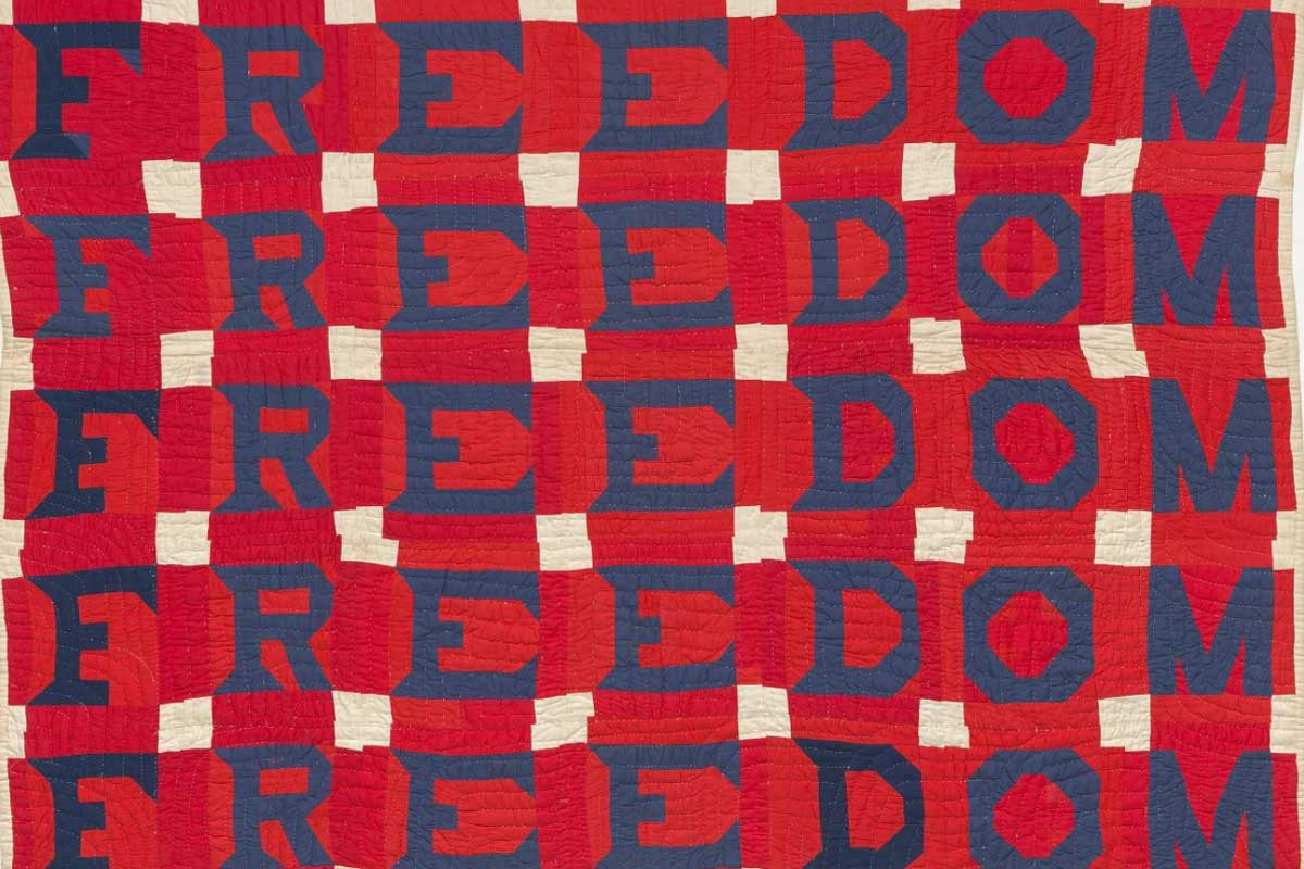 Blue stitched lettering spelling Freedom on red fabric