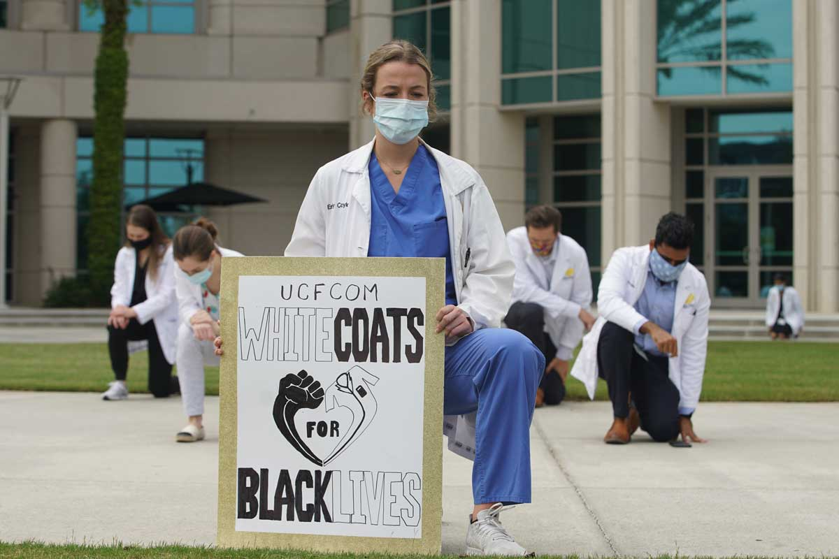 "Woman wearing doctor's white coat and face mask holds sign that reads ""White Coats for Black Lives"""