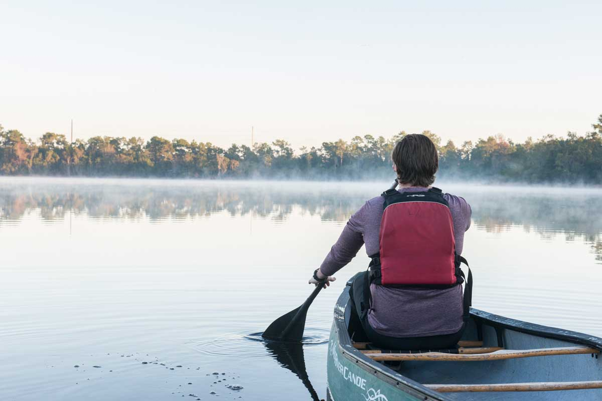 Man wearing life vest rows canoe on lake