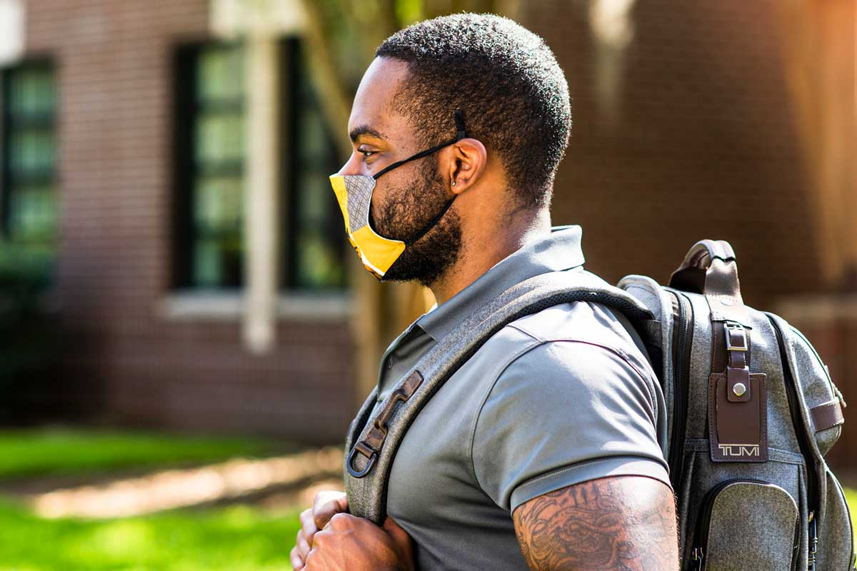 Man wearing backpack and face mask walks on UCF campus