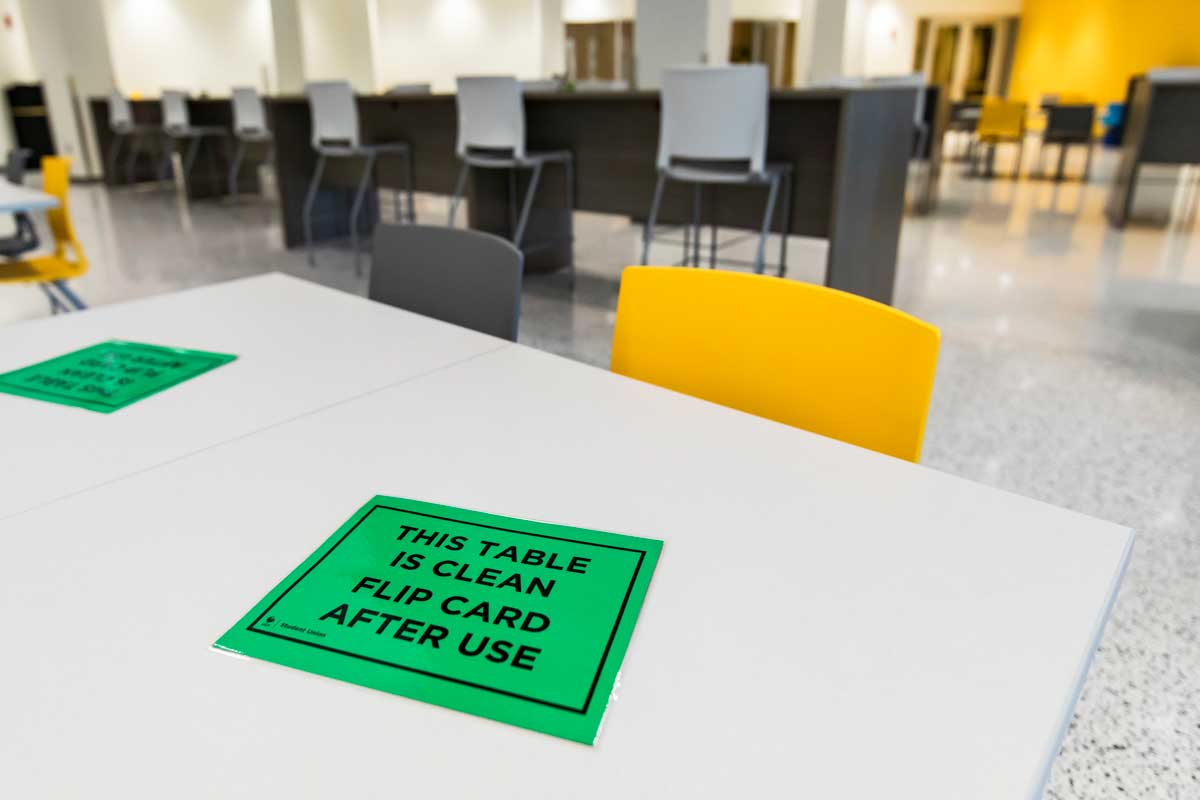 "table with green card that reads ""this table is clean. flip card after use"""
