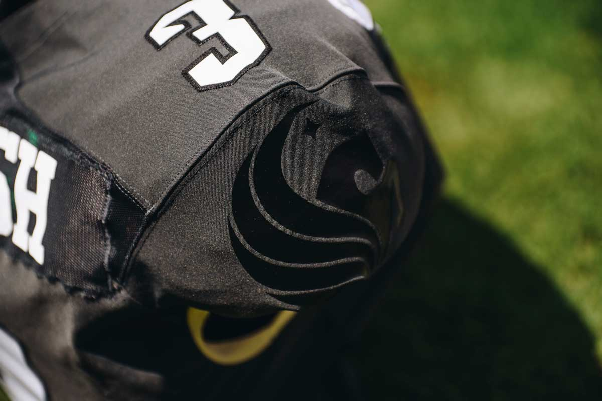closeup of black football jersey with Pegasus logo