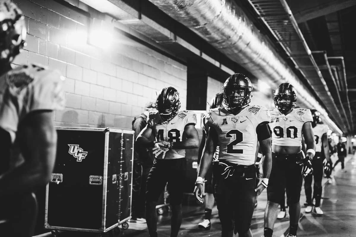 black and white photo of football team walking through tunnel at stadium