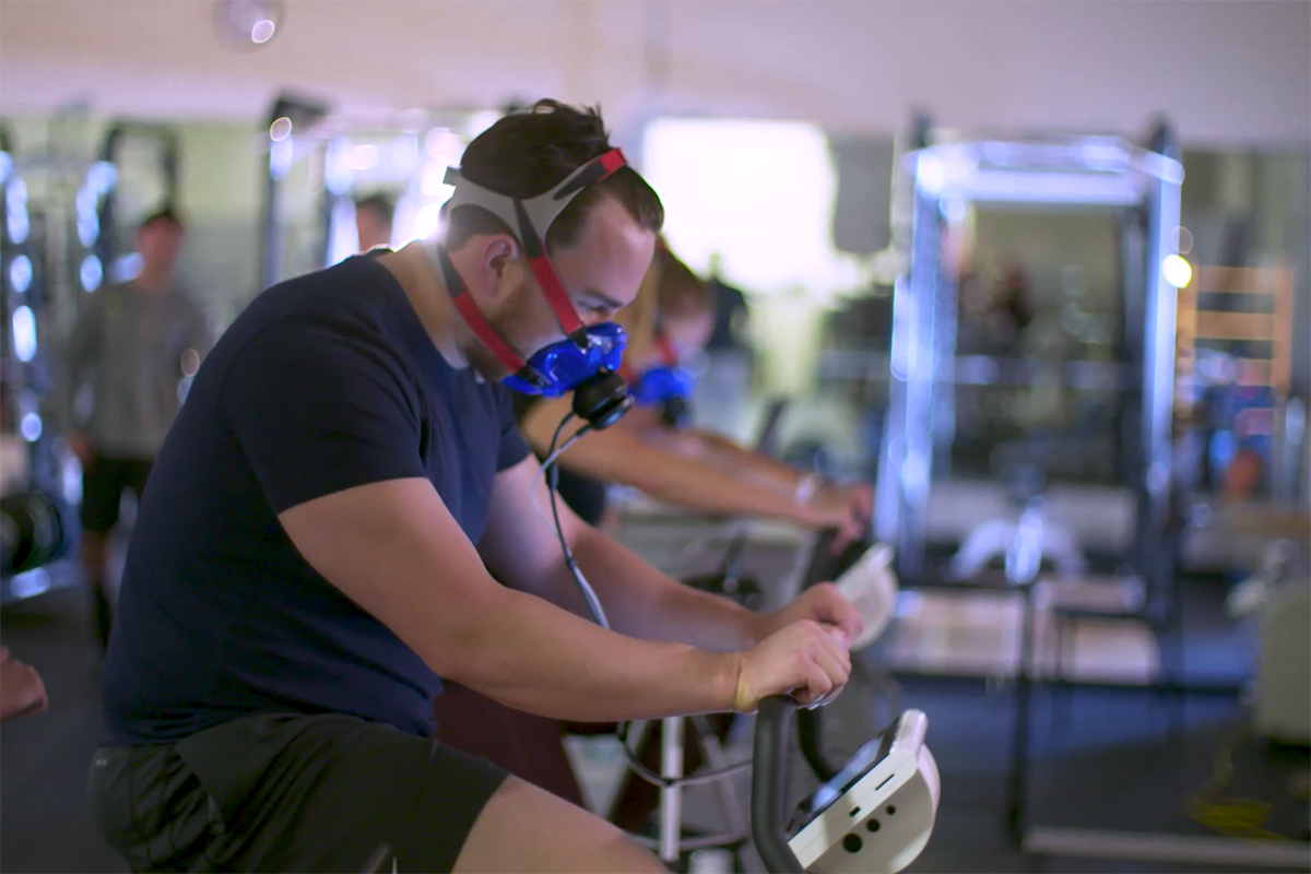 man rides exercise bike while wearing a face mask