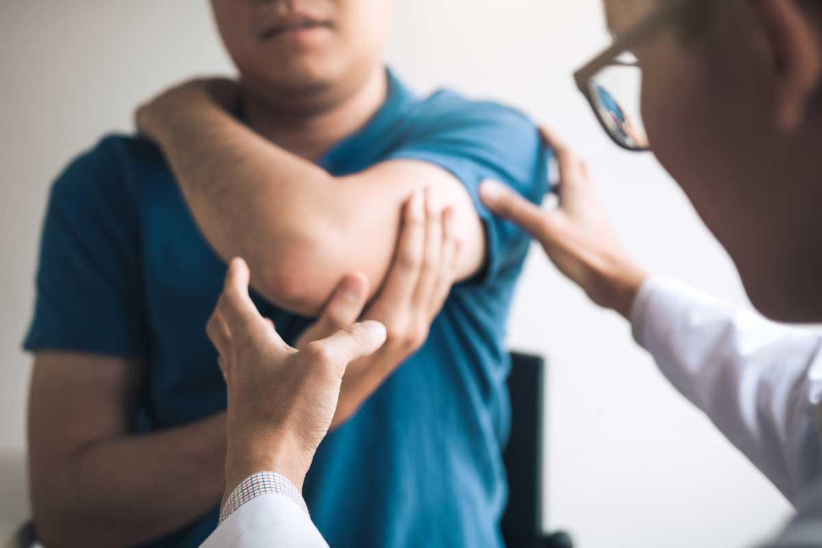 therapist examines a man's elbow