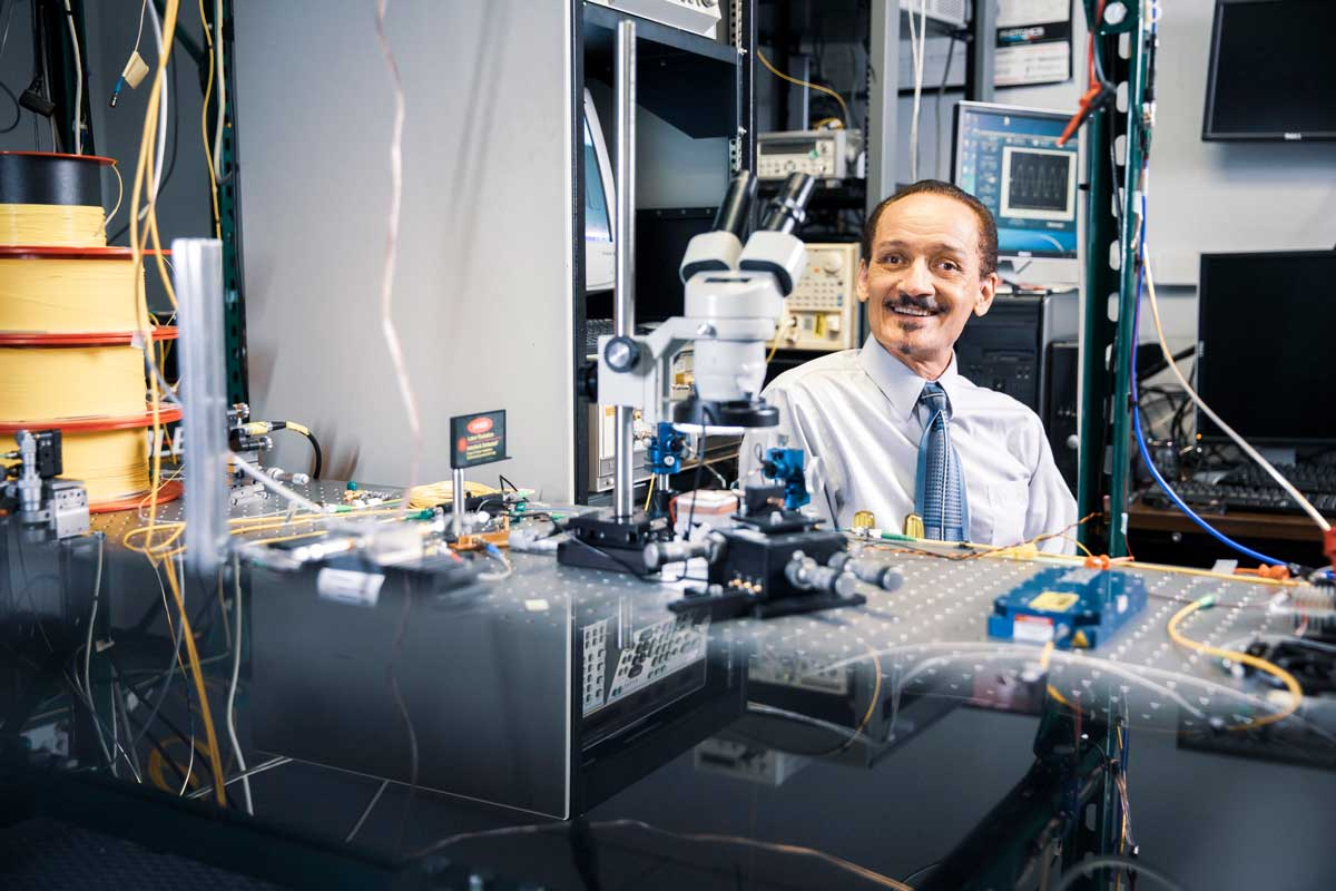 Peter Delfyett in a lab surrounded by computer and technical equipment