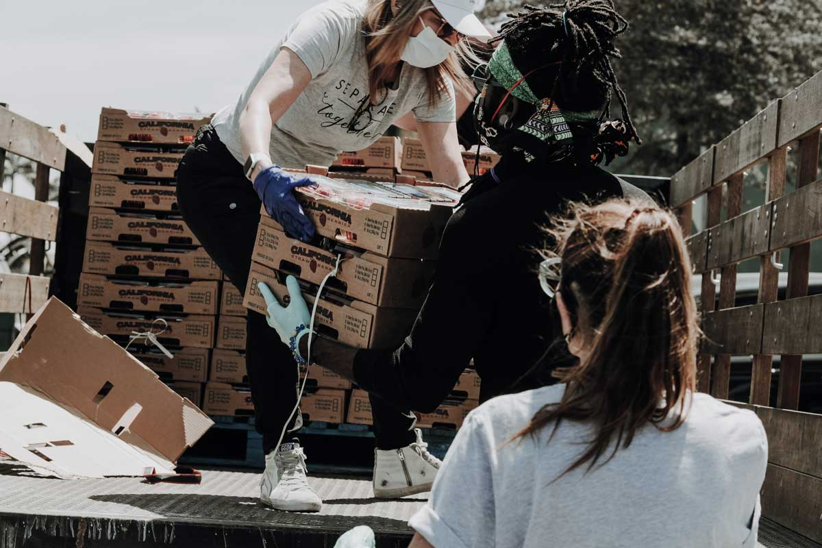 People work together to unload crates from truck