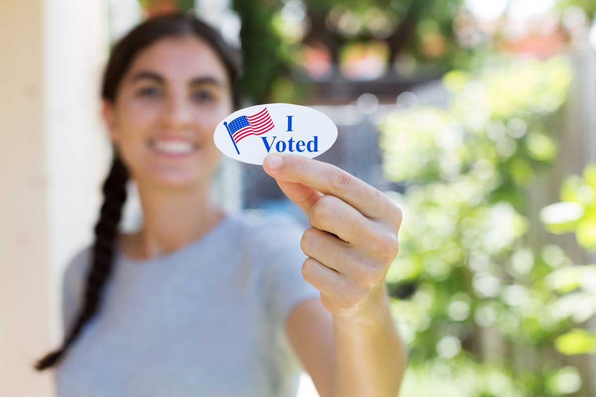 "Woman holds an ""I voted"" sticker"