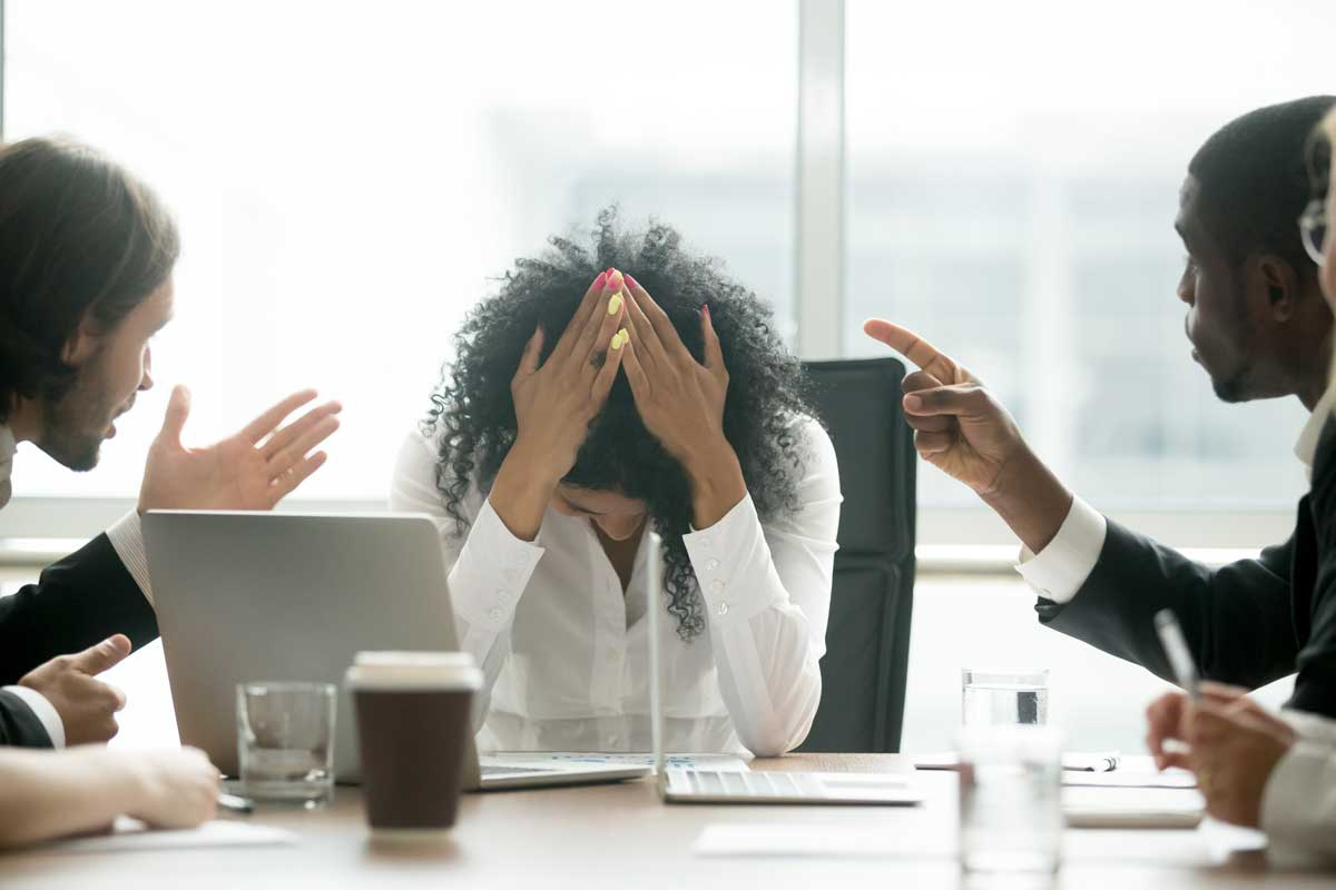 Two men sitting at conference table point at a woman, who has her hands on her head in frustration