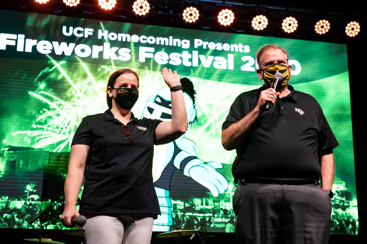 President Alexander N. Cartwright and First Lady Melinda Cartwright hold microphones on stage