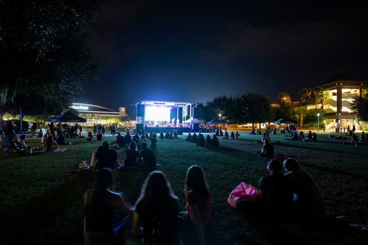 groups of people sit on Memory Mall with stage lit up at night