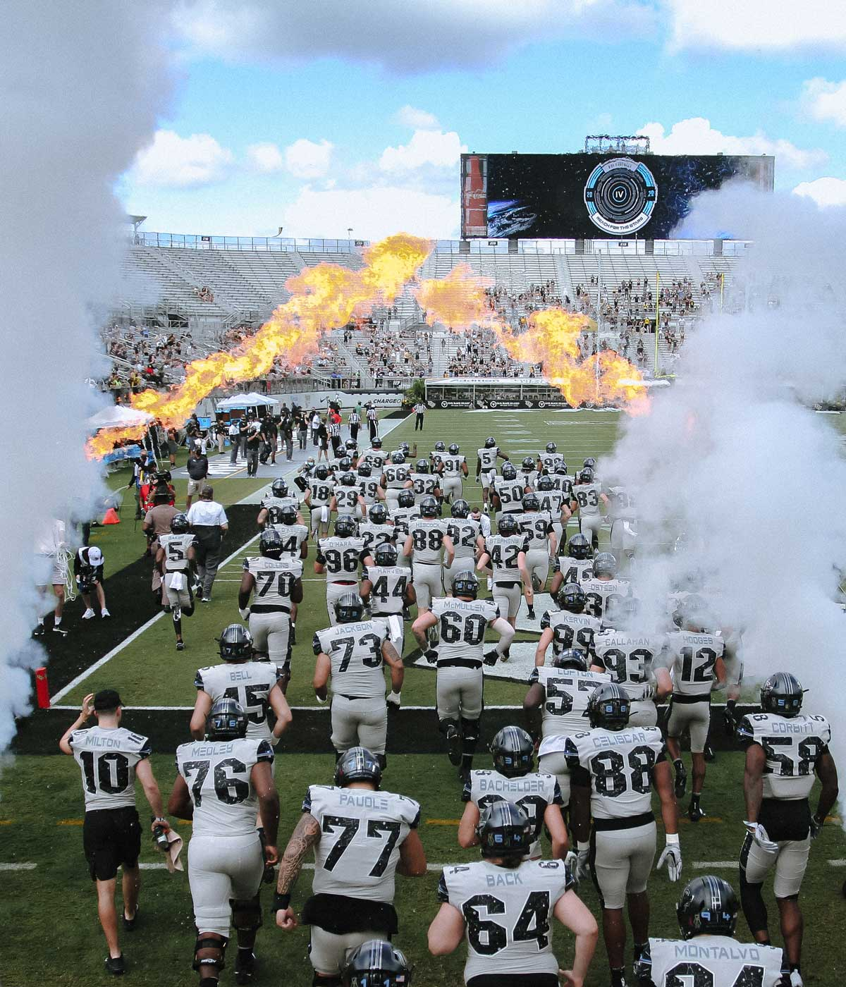 UCF football team runs onto the field with smoke and fire tunnel