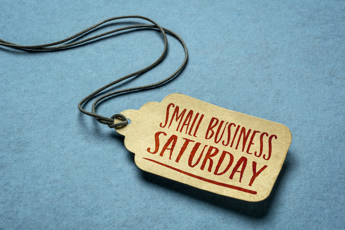 Small Business Saturday sign - a paper price tag with a twine against blue paper background, local holiday shopping concept (Small Business Saturday sign - a paper price tag with a twine against blue paper background, local holiday shopping concept, A