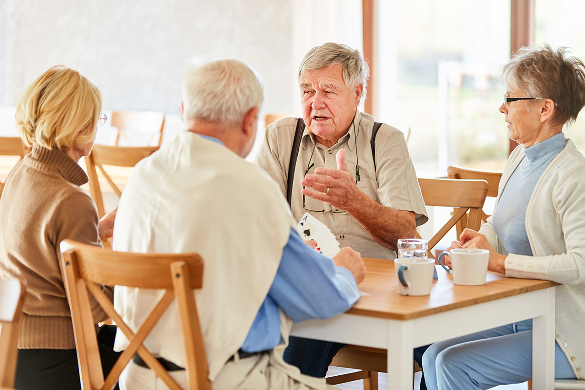 Older adults sitting at a table and talking