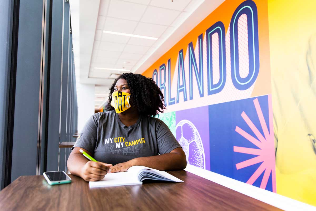 Student wearing yellow face covering sits with an open book in front of a colorful wall