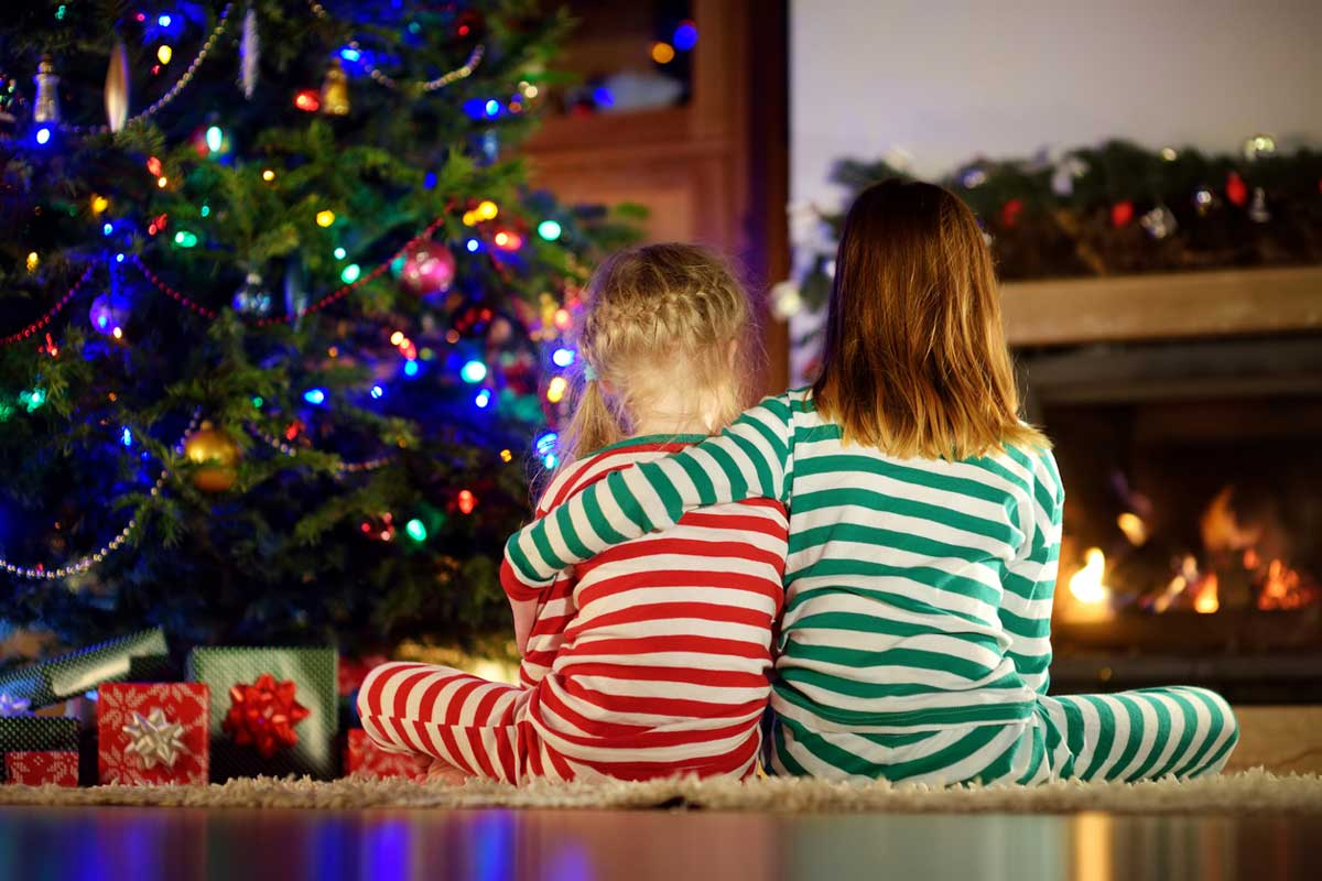 Two young girls in stripped pajamas, one arm around the shoulders of the other, sit by a Christmas tree
