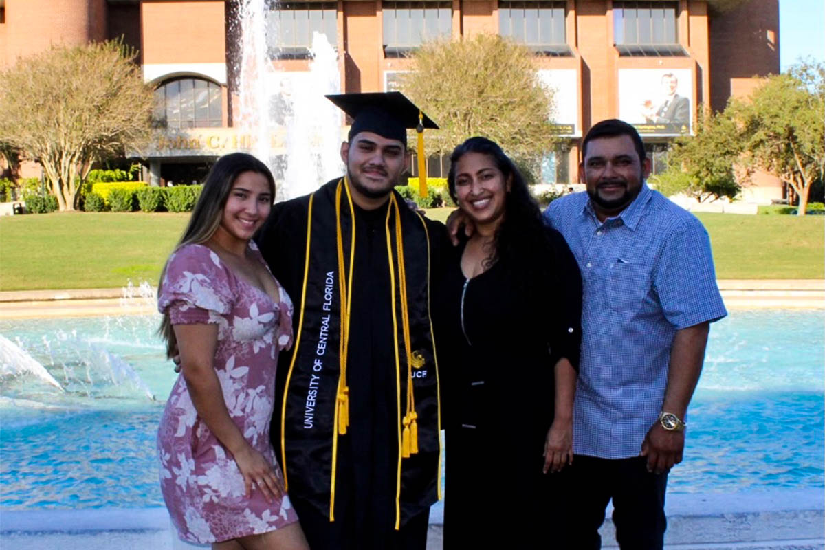 A student wears a cap and gown while posing for a photo with his family.