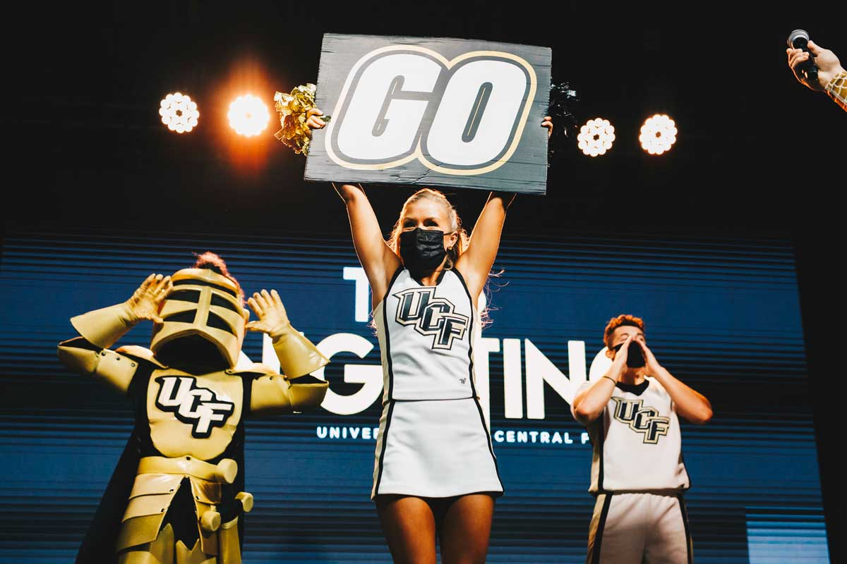 "UCF cheerleaders and Knightro pump up crowd with sign reading ""go"""