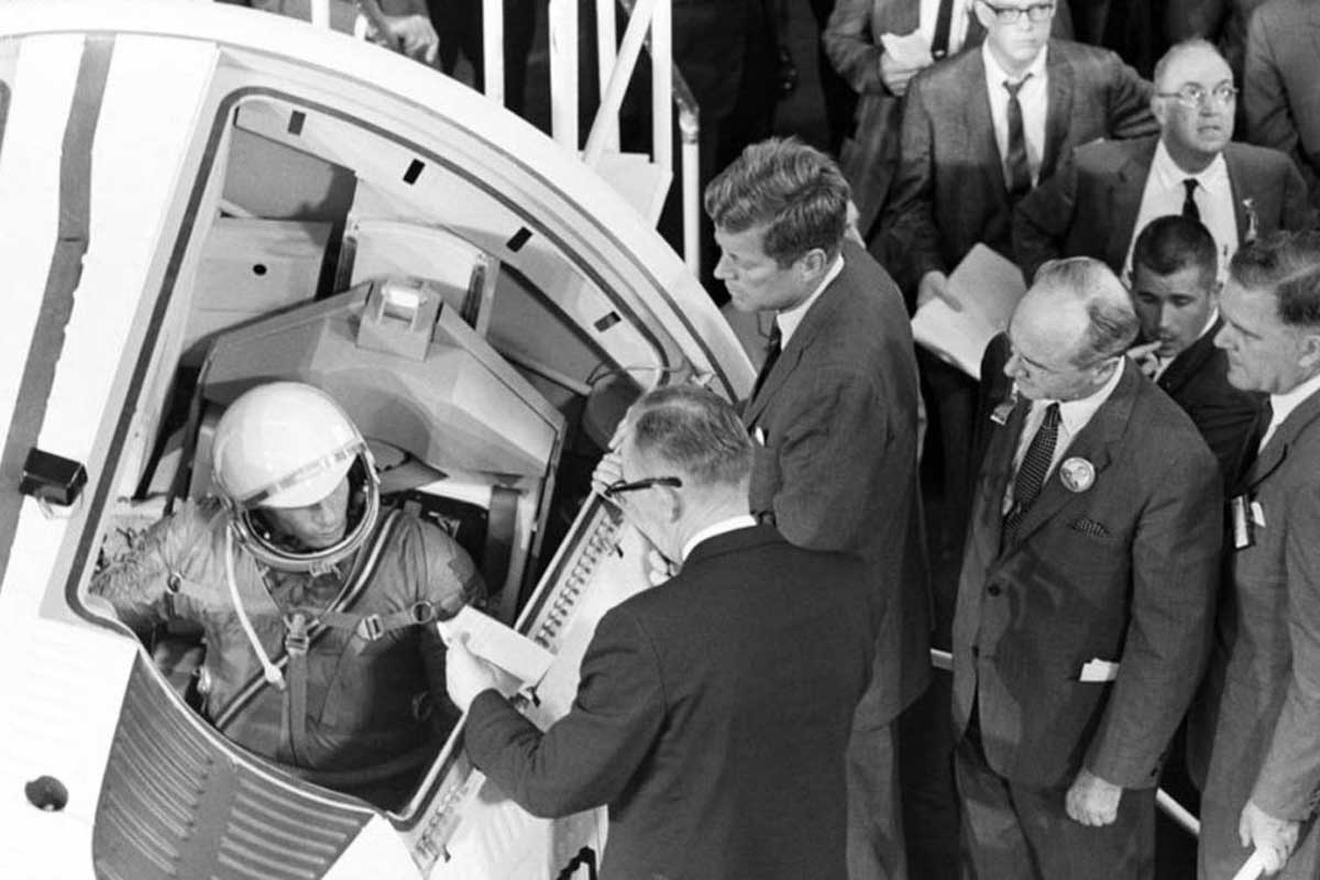 Black and white photo of President John F. Kennedy visiting an astronaut seated in a rocket.
