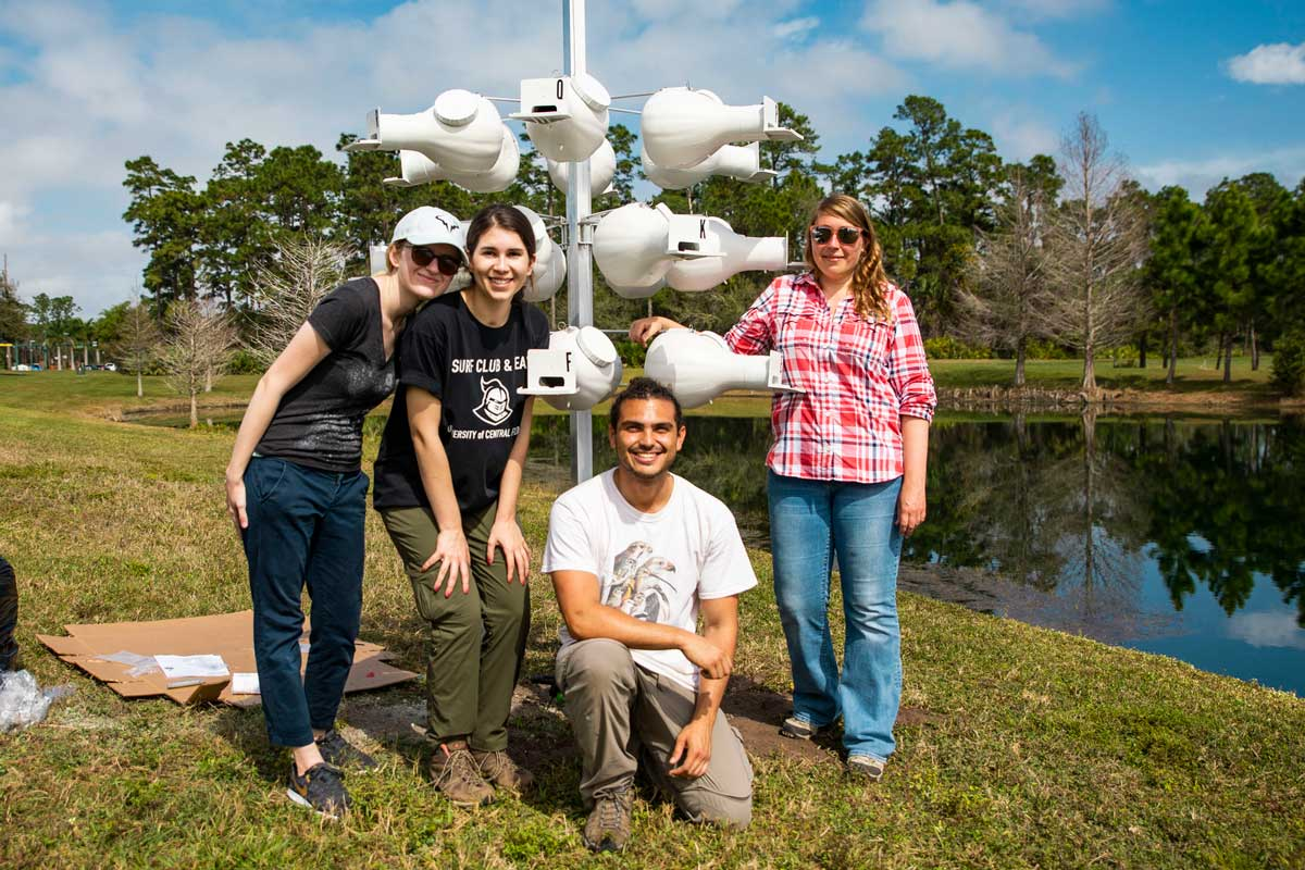 Four biology students pose with white bird houses