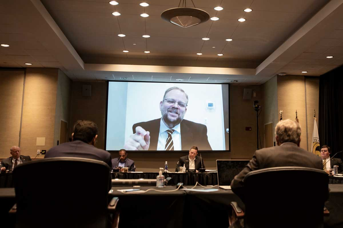 Alexander N. Cartwright addresses conference room from large video screen