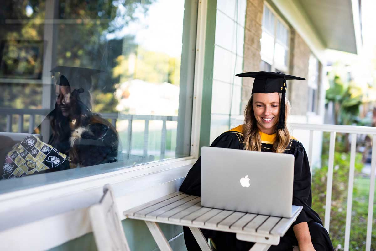 Woman in cap and gown sits on front porch with her Mac laptop as dog inside the home looks at her through a window