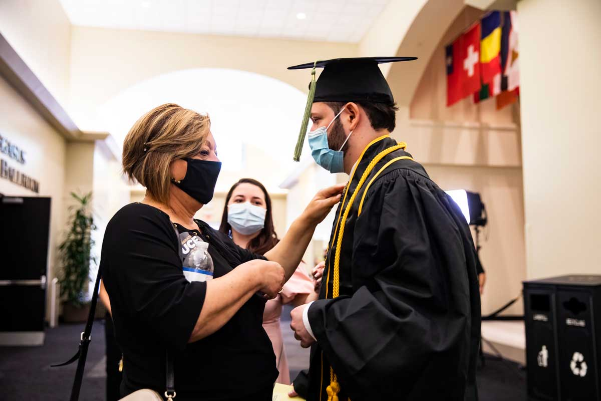 A blonde woman straightens her son's cap and gown