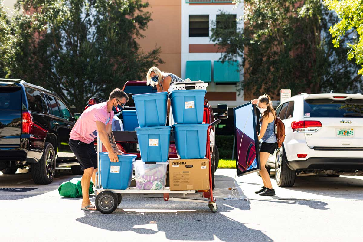 Parents help daughter move into UCF Housing, loading bins on a dolly in front of their car